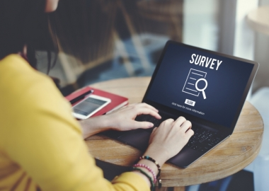 Woman with laptop that says survey