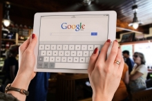 Woman holding tablet with Google homepage